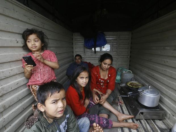 Com medo de novos tremores, família passam a viver dentro de carros e caminhões (Foto: Bikram Rai / AP)