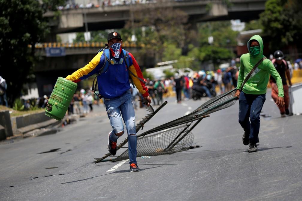 Oposicionistas do governo Maduro constroem barricadas em protesto (Foto: REUTERS/Carlos Garcia Rawlins)