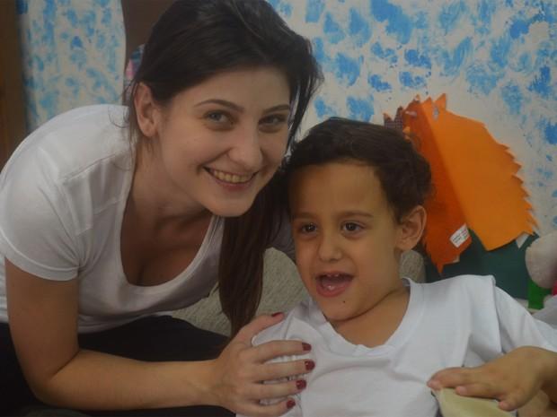 A terapeuta ocupacional Paola Segati com Felipe Rondi em entidade em Ribeirão Preto (Foto: Rodolfo Tiengo/ G1)