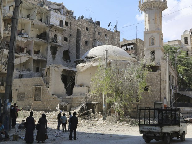 Moradores observam mesquita bombardeada em um distrito de Aleppo nesta terça-feira (3), dia de eleição (Foto: Mahmoud Hebbo/Reuters)
