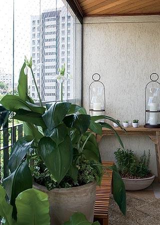 Vista do corredor estreito, a varanda nem parece ser tão  pequena. Ganhou banco do designer Fernando Jaeger e  aparador, donzelas e vasos de terracota da L'Oeil (Foto: Casa e Jardim)
