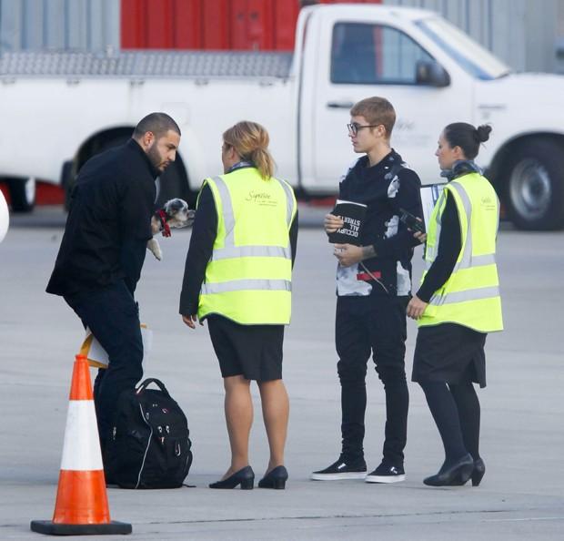 Bieber deixa o avião e deixa segurança levar seu cachorro (Foto: Grosby Group)