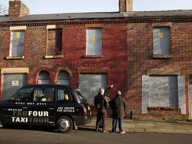 Guia aponta para a a casa (à dir.) em que Ringo Starr, dos Beatles, morou entre os 3 e os 21 anos de idade, em Liverpool, na Inglaterra; fã da banda comprou imóvel por cerca de R$ 364 mil (Foto: Phil Noble/Reuters)