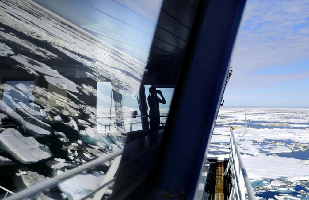 Estagiário observa com a ajuda de um binóculo enquanto a MSV Nordica quebra o gelo da região noroeste do Ártico. (Foto: David Goldman/AP Photo)