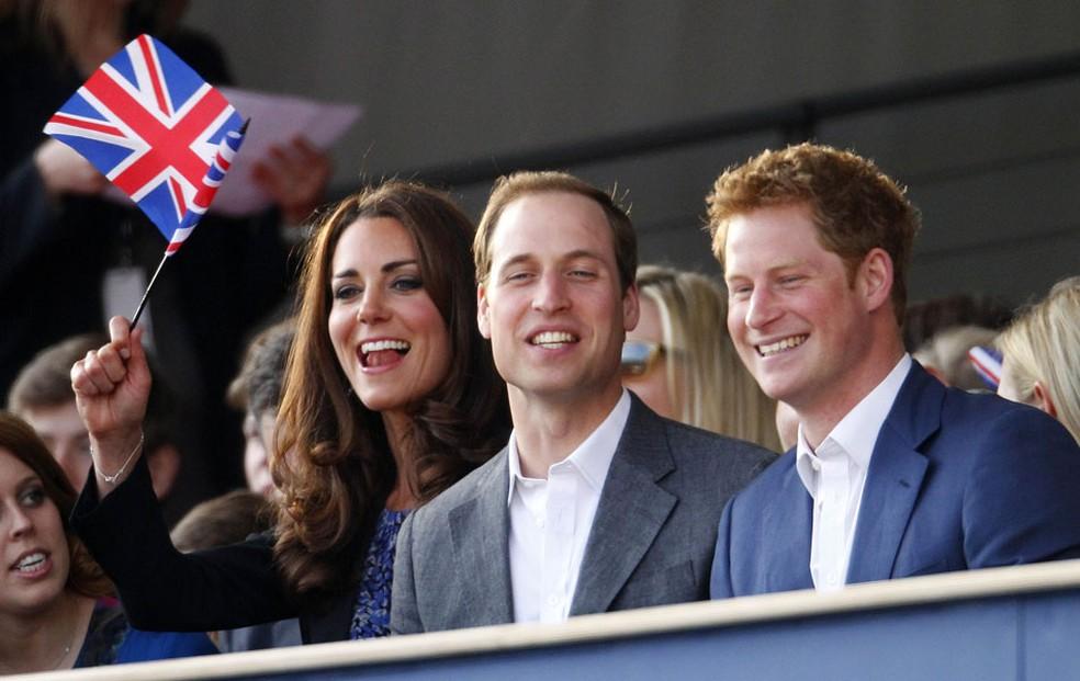 Em imagem de arquivo,  William e Kate (esq.) se divertem ao lado do príncipe Harry durante a celebração de um grande show em frente ao Palácio de Buckingham (Foto: Dave Thompson/AP)