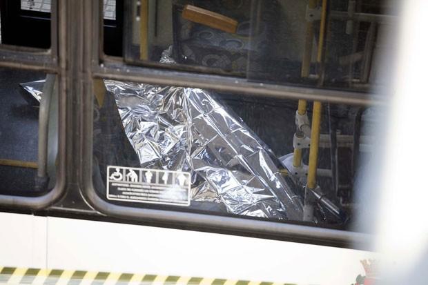 Corpo de vítima foi coberto dentro do ônibus após a chegada da polícia ao local da ocorrência, na Avenida Nove de Julho (Foto: Mario Ângelo/Sigmapress/Estadão Conteúdo)