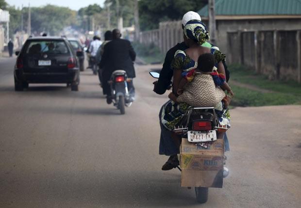 Uma mulher foi flagrada viajando em uma mototáxi nesta terça-feira (29) na cidade de Kaduna, na Nigéria, enquanto levava seu filho em suas costas.  (Foto: Akintunde Akinleye/Reuters)
