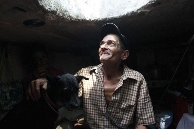 Quando chove, casal usa uma tampa de bueiro para evitar que a casa seja alagada. (Foto: Albeiro Lopera/Reuters)