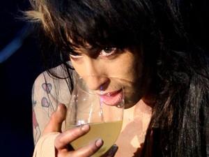 Em 30 de maio de 2008, Amy Winehouse toma um drinque durante apresentação no Rock in Rio Lisboa (Foto: Steven Governo/AP)