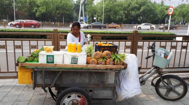 Vendedora de fruta em rua de Pequim tem o QR Code que permite o pagamento por meio do celular (Foto: Ana Cristina Campos/Agência Brasil )