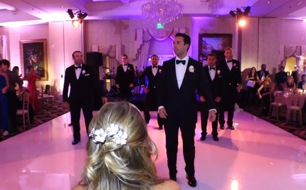 Sean dança com os padrinhos ao fundo enquanto a noiva observa (Foto: Reprodução/YouTube)
