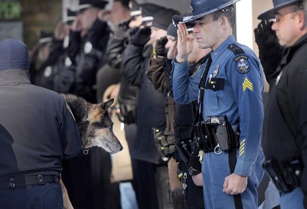 Sargento Robert Burke, da Polícia do Estado do Maine, saúda, ao lado de outros policiais, o cão policial Sultan, carregado pelo oficial Shane Stephenson até a clínica veterinária onde seria sacrificado  (Foto: AP Photo/The Press Herald, Shawn Patrick Ouellette)