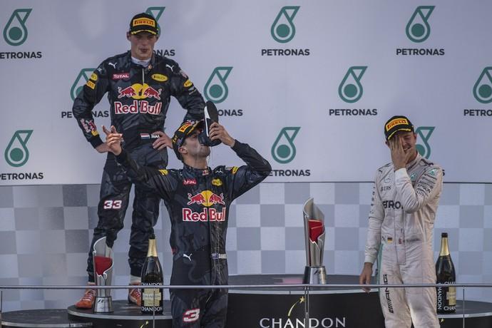 Daniel Ricciardo faz o shoey sendo observado por Nico Rosberg no pódio do GP da Malásia (Foto: AFP)