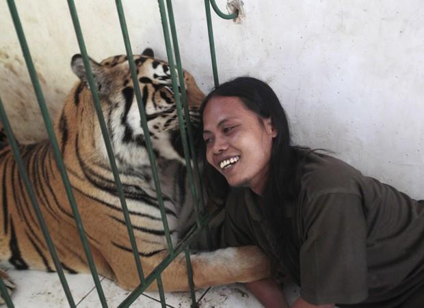 Tratadora Soleh cuida de tigre 'mascote' de escola islâmica na Indonésia. Animal é alimentado por ela desde que tinha três meses de idade, segundo a Reuters (Foto: Sigit Pamungkas/Reuters)