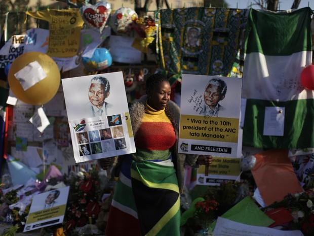 Mulher segura cartaz de Mandela em frente ao hospital em que ele está internado em Pretória neste sábado (29). (Foto: Muhammed Muheisen/AP)