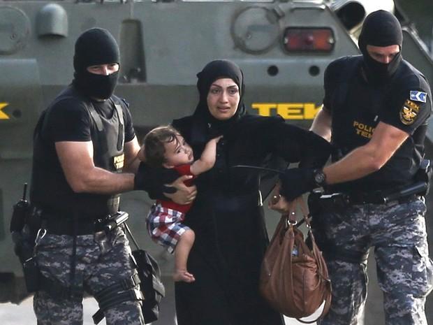 Policiais húngaros levam mulher e criança migrantes durante confronto em Roszke, na Hungria. Após a polícia húngara passar a bloquear a entrada de migrantes, grupos que estavam acampados do lado sérvio começaram um protesto seguido do confronto (Foto: Dado Ruvic/Reuters)
