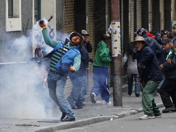 Manifestante lança bomba contra policiais em La Paz, na Bolívia (Foto: AP)