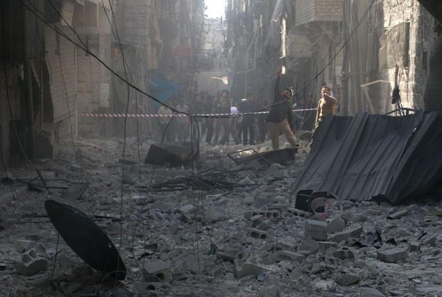 Sírios caminham em meios a escombros em rua na cidade de Aleppo  (Foto: Baraa Al-Halabi/AFP)