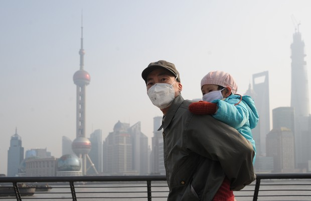 Homem carrega criança nas costas em Xangai, China. Os dois usam máscaras por conta da forte nuvem de poluição na cidade (Foto: ChinaFotoPress via Getty Images)