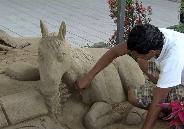 Artista trabalha em presépio feito de areia em Santos, SP (Foto: Reprodução/TV Tribuna)
