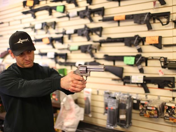 Brandon Wexler mostra a um cliente uma das armas a venda na loja K&W Gunworks, em Delray Beach, na Flórida (Foto: Joe Raedle/Getty Images/AFP)