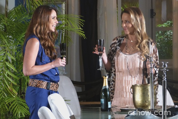 A loira conta para a amiga o motivo de tanta alegria (Foto: Em Família / TV Globo)