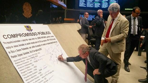 Deputados assinam cartaz fixado no plenário da Câmara no qual se comprometem a comparecer à sessão que pode cassar Cunha (Foto: Sara Curcino/G1)