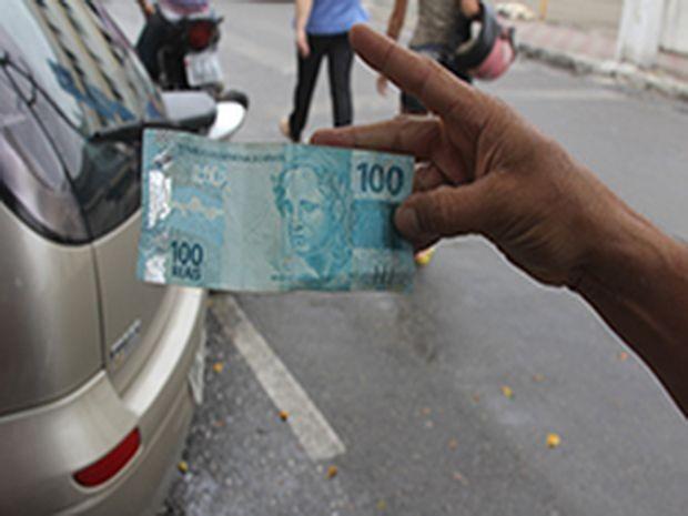 Popular mostra dinheiro que pegou na praça (Foto: Lagartense)