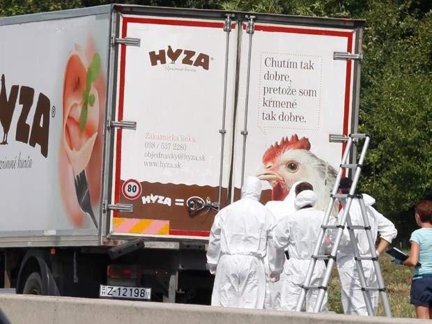 Autoridades forenses isolam caminhão  estacionado em estrada da Áustria em que dezenas de imigrantes foram encontrados mortos (Foto: AFP PHOTO / DIETER NAGL)