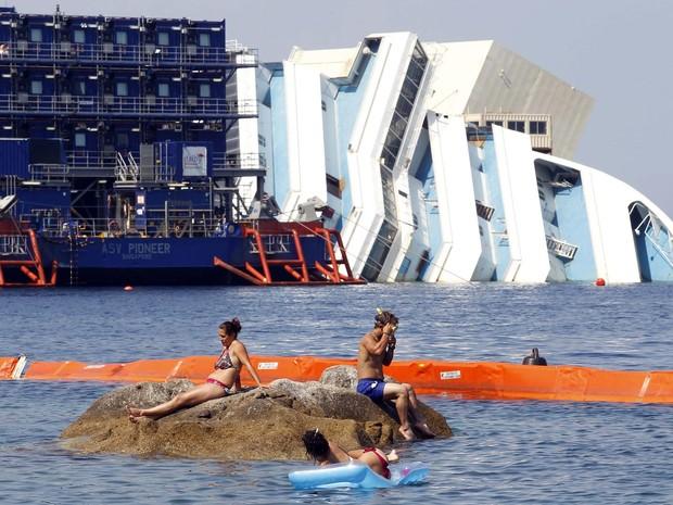 Banhistas aproveitam dia de sol descansando em rocha próxima ao navio Costa Concordia, que permanece há um ano e meio tombado à beira da ilha de Giglio, na Itália. (Foto: Giampiero Sposito/Reuters)