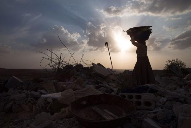 Mulher em meios aos escombros em Kobane (Foto: Gabriel Chaim/G1)