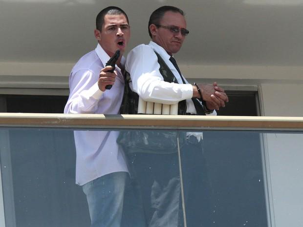 Sequestrador armado mantém refém em sacada de hotel em Brasília. Colete da vítima tem objetos cilíndricos que supostamente seriam bananas de dinamite (Foto: Ueslei Marcelino/Reuters)