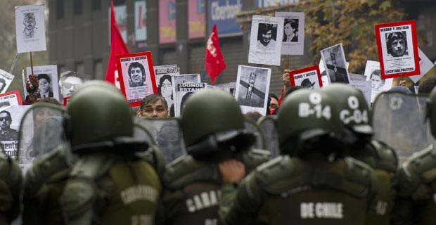 Manifestantes com fotos de mortos e desaparecidos no regime militar protestam neste domingo (10) em Santiago do Chile contra homenagem ao ex-ditador Augusto Pinochet (Foto: AFP)