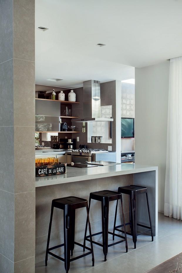Cozinha | O espaço onde a família faz refeições rápidas tem bancada de Corian, da Futura Superfícies. Banquetas e bandeja de copos da Velha Bahia (Foto: MCA Estúdio)