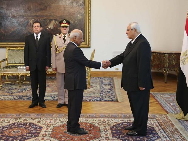 16/7 - Presidente interino do Egito Adli Mansour aperta a mão do novo primeiro-ministro interino Hazem El-Beblawi durante posse no palácio presidencial no Cairo. (Foto: Presidência do Egito/Reuters)