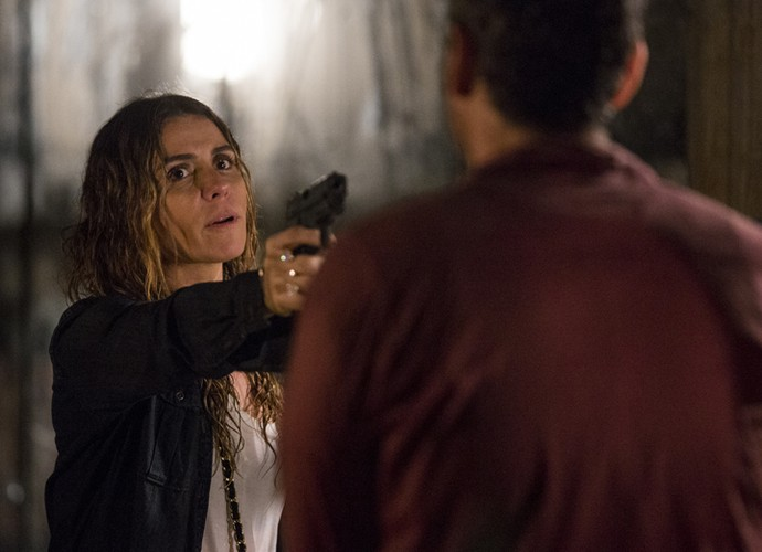 Atena consegue virar o jogo e aponta arma para Romero (Foto: Ellen Soares/ Gshow)