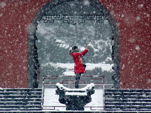 Mulher faz selfie durante nevasca em Lin'an, na província de Zhejiang (Foto: Chinatopix/AP)