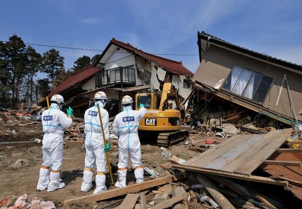 Agentes inspecionam os destroços de residências próximas à usina nuclear de Fukushima, no Japão (Foto: The Asahi Shimbun/Getty Images)
