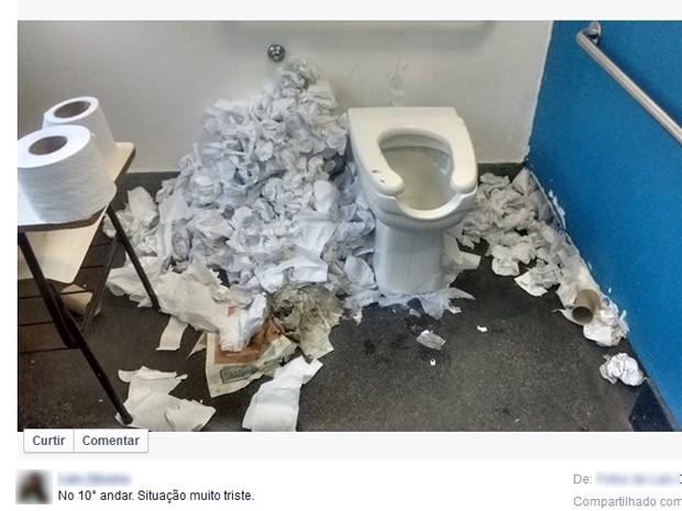 Foto com montanha de papel higiênico no chão do banheiro foi postada por estudante (Foto: Reprodução / Facebook)