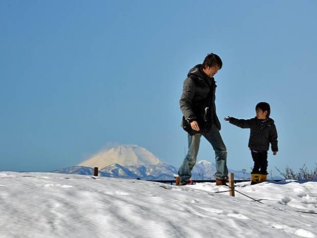 Um menino e seu pai andam em um campo coberto de neve em Tóquio, aos pés do Monte Fuji. (Foto: Yoshikazu Tsuno / AFP Photo)