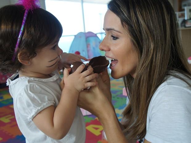 Fernanda Pontes come chocolate com a filha vestida de coelhinha (Foto: Flor do Caribe / TV Globo)
