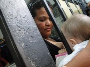 Em ocupação da Prefeitura de BH, mãe amamenta filha pela grade do prédio da administração pública. (Foto: Pedro Ângelo/G1)