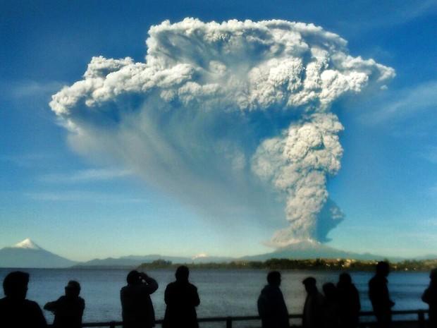 Pessoas observam de Puerto Varas, no Chile, a coluna de cinzas e lava do vulcão Calbuco, na quarta-feira (22) (Foto: AFP Photo/Giordana Schmidt)