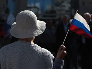 Mulher acena com bandeira russa em comemorações de Moscou, nesta quarta (22) (Foto: Reuters)