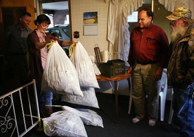 Josh e Tara Ferrin mostram as sacolas de dinheiro para Dennis e Kay Bangerter. (Foto: Brian Nicholson/Deseret News/AP)