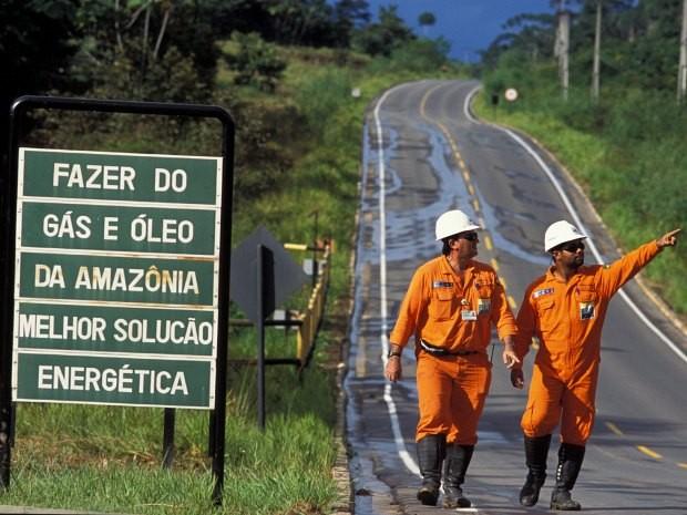 Funcionários caminham ao lado de placa na estrada Urucu, na bacia petrolífera de mesmo nome (Foto: Divulgação/Petrobras)