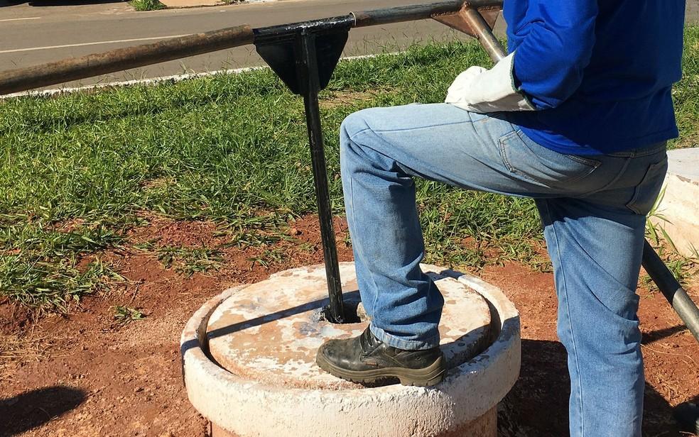 Técnico da Caesb espera para girar válvula de registro e liberar o fluxo de água (Foto: Luiza Garonce/G1)