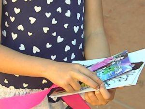 Menina mostra o CD e a foto autografada que ganhou do cantor.  (Foto: reprodução/TV Tem)