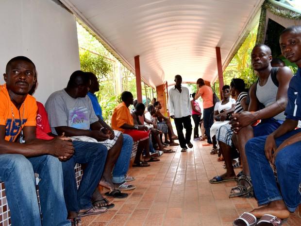 Imigrantes na entrada do abrigo, em Rio Branco (Foto: Aline Nascimento/G1)