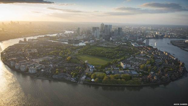 """Ao leste de Londres, a ilha circundada por canais aquaviários e o Rio Tâmisa chamada de """"Isle of Dogs"""". À frente da área está o parque de Mudchute e, ao fundo, os arranha-céus da região de Canary Wharf.  (Foto: Jason Hawkes)"""